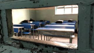 Some blue desks with books on in a classroom