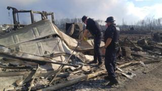 Emergency workers inspect burnt-out buildings in Fort McMurray
