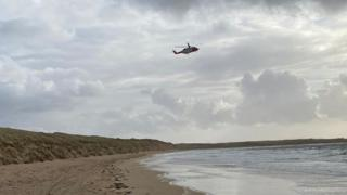 A helicopter flying over Bunbeg beach