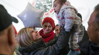 Tima Kurdi lifts up her nephew at Vancouver airport. 28 Dec 2015