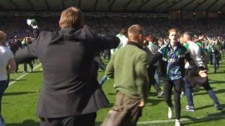 Greg Binnie (right in Hibs top and tracksuit) runs towards Hibs manager Alan Stubbs (left - back to camera)after the pitch invasion