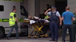 Emergency services personnel transport a stretcher carrying a person at a hospital in central Christchurch, New Zealand