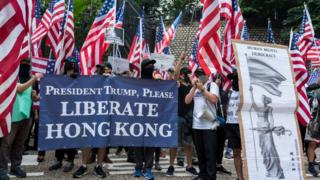 """معترضان دموکراسی خواه هنگ کنگ پلاکاردهایی در دست داشتند که بر روی آن نوشته بود """"رئیس جمهور ترامپ، لطفاً هنگ کنگ را نجات دهید"""" و """"عظمت را به هنگ کنگ برگردانید"""""""