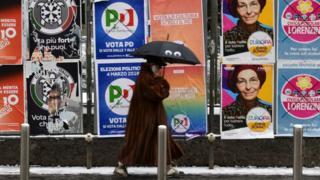 Seçim posterleri önünde yürüyen bir kişi