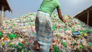 رجل وسط كومة من زجاجات البلاستيك