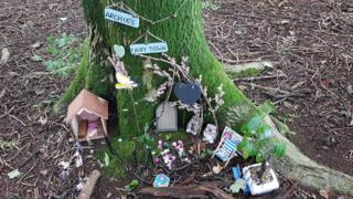 """A miniature door, house and decorations at the base of a tree with a sign for """"Archie's fairy town"""""""