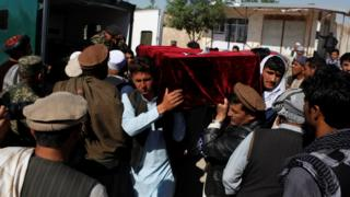 Relatives carry the body of one of the victims of a Taliban attack on an Afghan military base