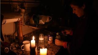 Mulher acende velas para ter luz durante o apagão na Argentina