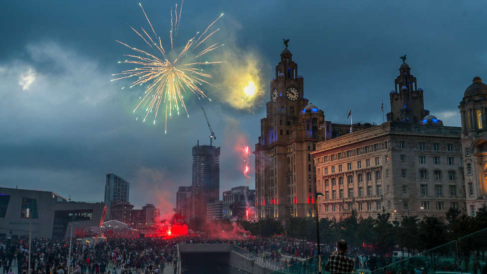 Firework lights up sky outside Liver Building
