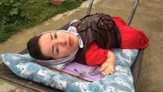 Mitra, a 41-year-old woman, living with 75 per cent physical disabilities on a cot. She is wearing a red dress and a brown jacket in the picture.