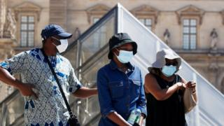 People wearing protective masks walk near the Louvre in Paris