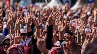 People cheer and flash a four finger sign called 'the rabia sign' as the Turkish president delivers a speech in Istanbul, on April 15, 2017, during a rally on the eve of the constitutional referendum