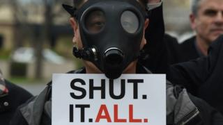 A Porter Ranch resident wearing a gas mask as he joins others in a protest outside a meeting of the Air Quality Management Board (23 January 2016)