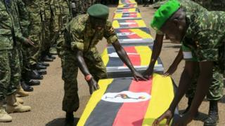 Uganda army soldiers lay national flags on the caskets carrying the remains of Ugandan soldiers who were killed in Somalia this week, at a military airbase in Entebbe on 3 September 2015