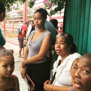 Pessoas nas proximidades do porto de La Guaira, na Venezuela, à espera de assistência médica