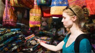Jovem mulher observa artesanato