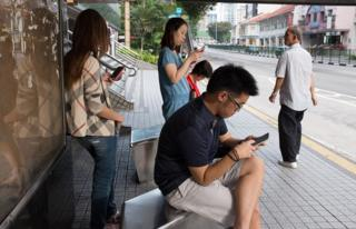 Commuters texting on their cellphone while waiting for public transport in Balestier Road, Singapore