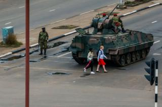 Young women walk past an armoured personnel carrier.