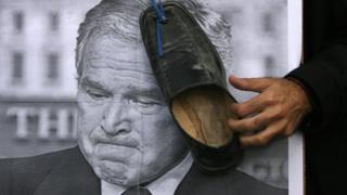 Zapato contra una foto de Bush.