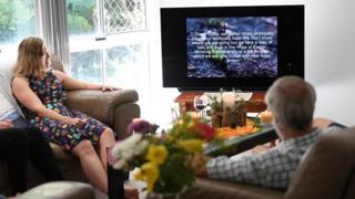 Darryl Nelson (R) and his daughter Monique (L) watch a liturgy sent to them by their church community as they celebrate Easter in their home in Brisbane, Australia