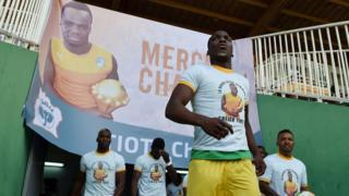 "Guinea""s National football team players enter the stadium under a poster of late football player Cheick Tiote at the stade de la paix in Bouake on June 10, 2017 during 2019 African Cup of Nations qualifyer football match between Ivory Coast and Guinea."