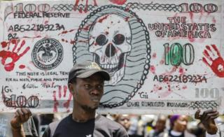 Kenyan activists raise a mock US dollar bill during a protest against the politicians and leaders of war-torn South Sudan, in Nairobi, Kenya, 11 October 2018.