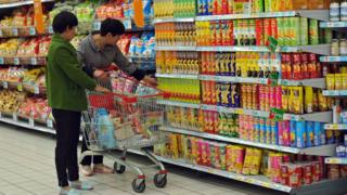 Customers select snacks at a supermarket in Fuyang, in eastern China's Anhui province