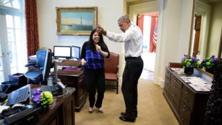 Obama dances, arms outstretched, with a staff member in the reception room adjacent to the oval office. The staff member is laughing looking directly at the camera.