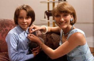 Lesley Judd pinning a gold Blue Peter badge onto a child.