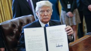 Trump imzayı gösteriyor