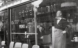 A waiter paints a sign in a restaurant window