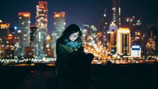 فتاة تطالع هاتفها الذكي وخلفها أضواء المدينة ليلا