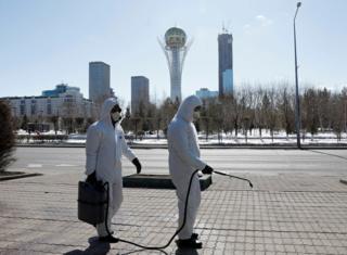 люди в костюмах химзащиты опрыскивают улицы