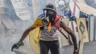 man in gas mask, draped in Venezuela flag, holding a spray can