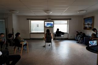 People watch TV in an empty room.