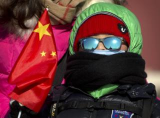 A boy in heavy winter clothing holds a Chinese flag as he stands in Tiananmen Square in Beijing, Saturday, 23 January 2016
