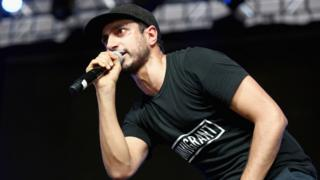 Riz Ahmed on stage in 2017