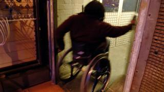 A man in a wheelchair going through a doorway
