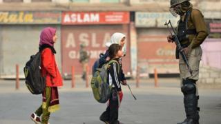 Anak sekolah Kashmir melewati paramilite India.