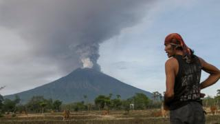 Hombre mira hacia el monte Agung, en alerta de erupción inminente.