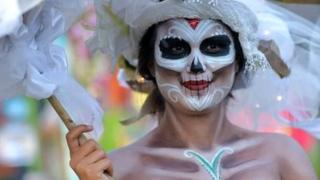 A woman in skeleton make-up carries and umbrella