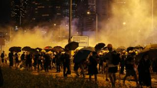 Protesters huddle as tear gas is fired