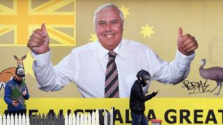 "A billboard ad for Clive Palmer shows him flashing a thumbs up in front of an Australian flag with text reading: ""Make Australia Great"""