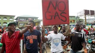 """Motorbike riders protest with a sign reading """"No Gas"""" at a petrol station in Monrovia, Liberia - Tuesday 28 January 2020"""