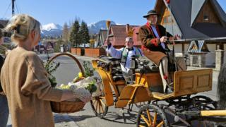 A priest sprinkles holy water on believers and their food while circuiting in a horse-drawn cart all over the vicinity during the celebrations of Holy Saturday in Zakopane, Poland