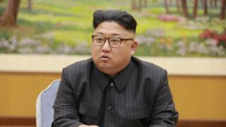 Kim Jong-un seen seated, wearing brown tortoiseshell glasses and a pinstripe dark grey suit