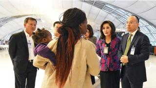 Thai airport officials talk to members of a Zimbabwean family