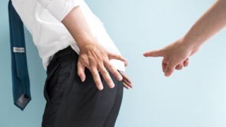Businessman points at colleague