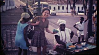 Em foto antiga, mulher aparece sorrindo ao lado de vendedora de quitutes baianos na rua