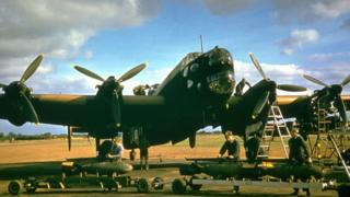 Circa 1940: Royal Air Force ground staff prepare to load a bomb onto a Handley Page Halifax